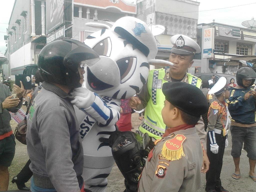 Salah seorang Pocil yang didampingi anggota Lantas Polres Konawe saat mengajarkan salah seorang pengendara cara memakai helm yang benar