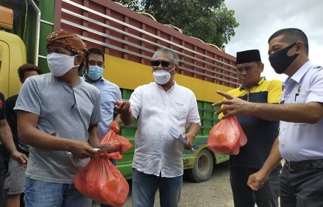Bupati Konawe Kery Saiful Konggoasa saat menyerahkan bantuan paket sembako kepada salah satu buruh muat di gudang Bulog Unaaha, Rabu (13/5/2020).