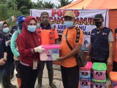 Penyerahan bantuan family kit dan hygiene kit oleh Ketua PMI Konawe Titin Nurbaya Saranani didampingi Plt. Kepala BPBD, Herianto kepada Kepala Desa Ambuulanu, Ketut Irawan